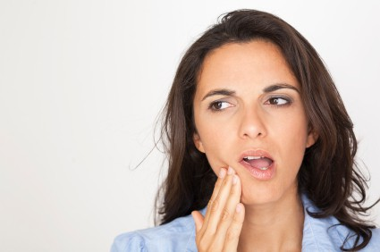Woman holding her mouth in pain due to a cyst in need of a visit to Henderson Oral Surgery & Dental Implant Center in Henderson, NV